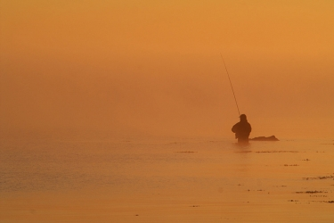 What a color! - This is the result of zooming in on a distant angler during sunrise on a very misty morning. When the sun cleared the horizon is blazed this extremely orange light through the mist and created this fantastic scene where sky and ocean blends so smoothly.