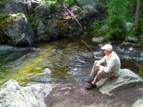 Contemplating Trout - Shane Murphy takes a few moments to himself watching an active trout feed against the rock wall.