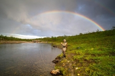 Under the rainbow - A fly-fisher framed by the multicolor arc