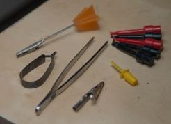 Assorted clips - For holding flies: post card clip, electronic clips, a hackle plier, tweezers. Combine with some play dough or a clamp, and your fly is fixed