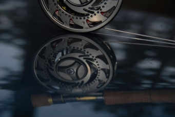 Abstract but clear - This reel waiting to go fishing was shot on a dark green car roof, playing with the reflection rather than the reel itself