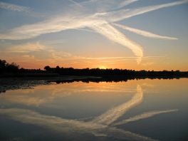 Trails - The sun is barely visible, and what makes this interesting is the airplane trails and the reflections
