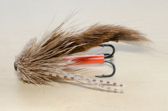 "Small Sea Trout Munker - Here the small, dark Sea Trout Munker is ""fake mounted\"" with a treble hook. For the hook to be properly mounted you need a tippet going through the fly and the orange junction tube. But this shows the look of the fly when it\'s fishing."