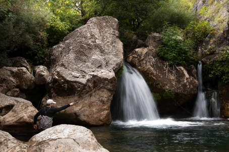 Fishing under a small waterfall -