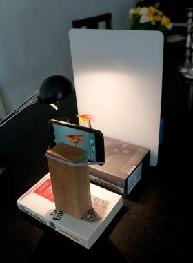 Smartphone setup - The phone is simply strapped to a wooden block using two rubber bands: one on the block to keep the phone from slipping and one to hold it. Simple, cheap and effective. The background is a nylon cutting board and the setup is built by books and cardboard boxes.