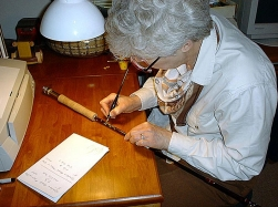 The writing process - Mary Lu Lewis writing on a rod. Patience and a steady hand is the key - and practice